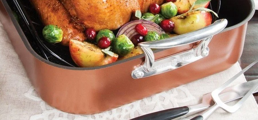 Photo of copper roasting pan with turkey and vegetables being cooked.