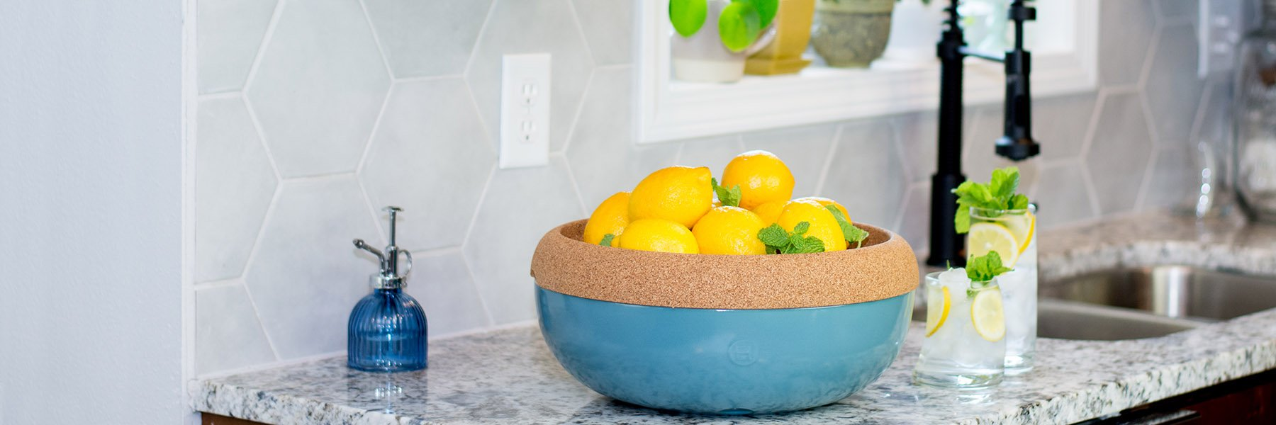 Photo of Emile Henry Blue Lagoon Storage Bowl with lemons and lemonade.