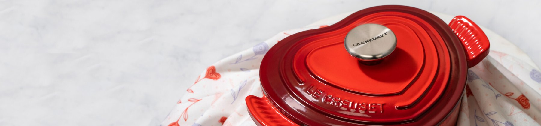 Le Creuset cerise red french oven, shaped like a heart.